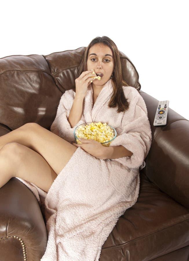 吃玉米花电视注意的妇女 库存图片