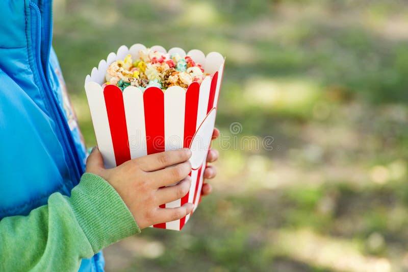 吃玉米花的小男孩 从桶一会儿的小男孩劫掠的玉米花 免版税库存图片