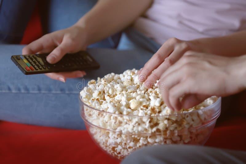 吃玉米花的年轻夫妇,当看着电视在晚上,特写镜头时 库存图片
