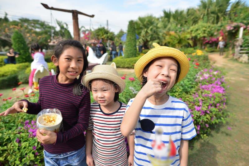 吃玉米花的愉快的亚洲孩子在公园 免版税库存图片