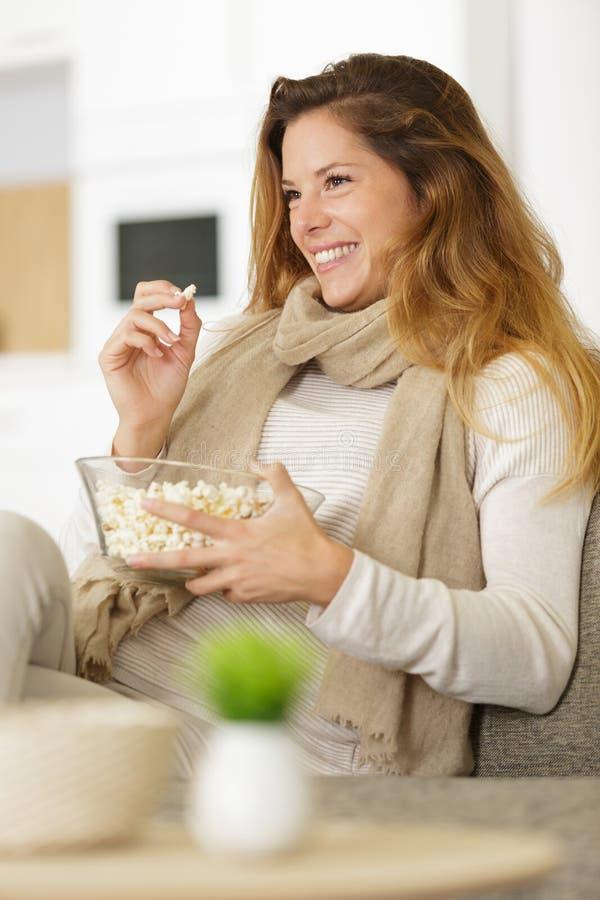 吃玉米花的愉快的妇女 免版税库存图片