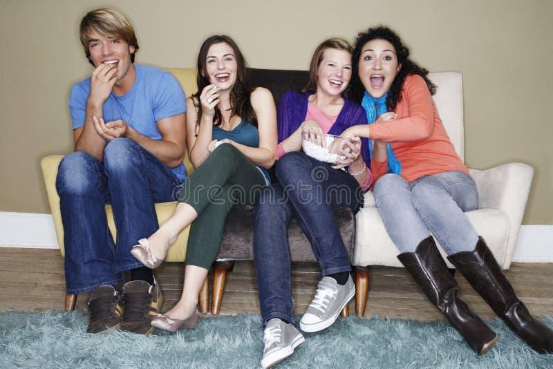 吃玉米花的朋友,当观看电影时 免版税库存照片