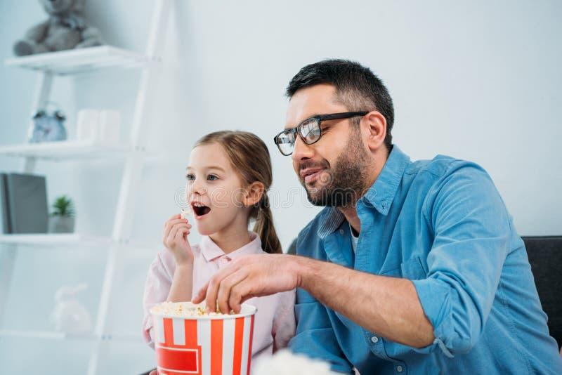吃玉米花的父亲和女儿,当一起时看电视 库存图片