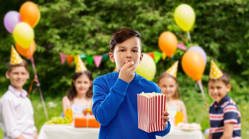 吃玉米花的男孩在生日宴会 库存照片