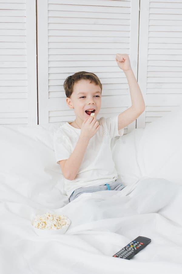 吃玉米花的男孩坐在床和看着电视上 免版税图库摄影