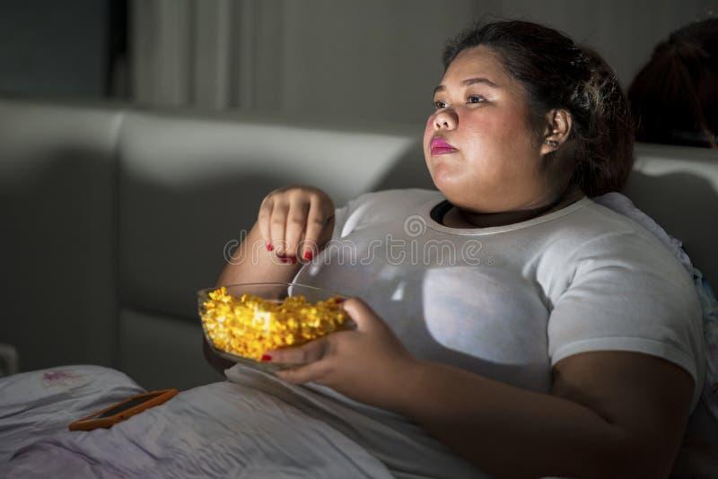 吃玉米花的肥胖妇女在卧室 库存图片