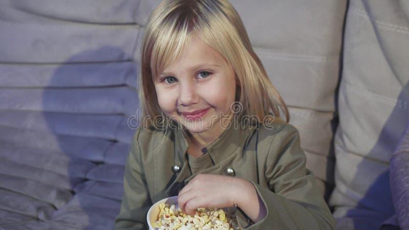 吃玉米花的逗人喜爱的小女孩微笑对照相机对戏院 免版税库存图片
