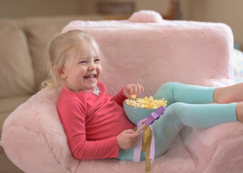 吃玉米花的逗人喜爱的小女孩,当在家时观看电影 库存照片