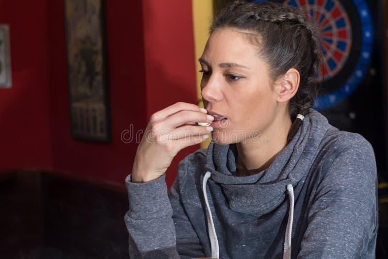 吃玉米花的年轻美丽的妇女 免版税库存照片