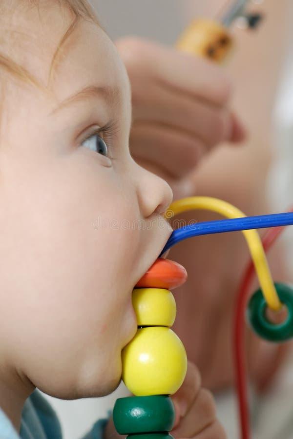 吃玩具的婴孩木 图库摄影
