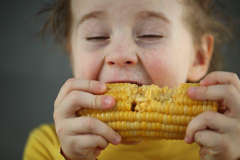 吃甜玉米的男孩金发碧眼的女人 免版税库存照片