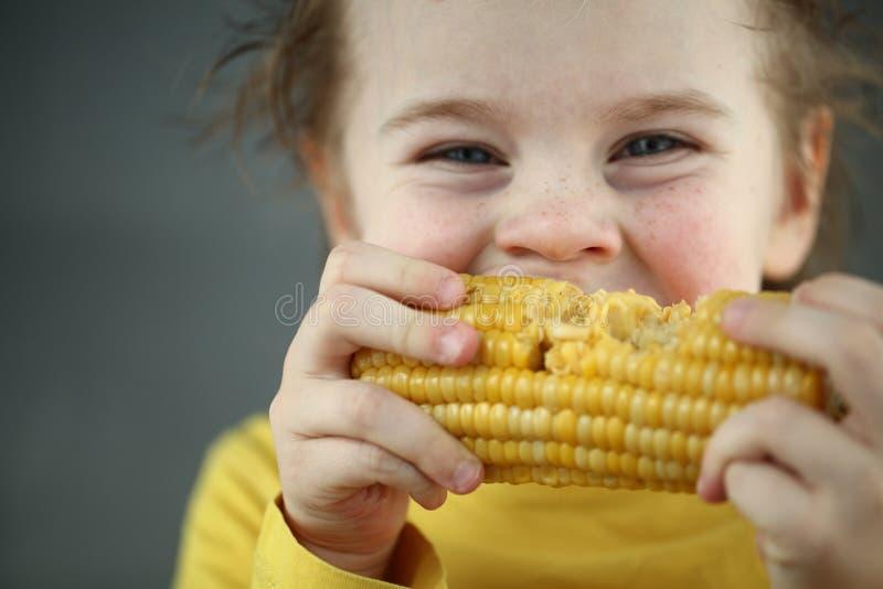 吃甜玉米的男孩金发碧眼的女人 库存图片