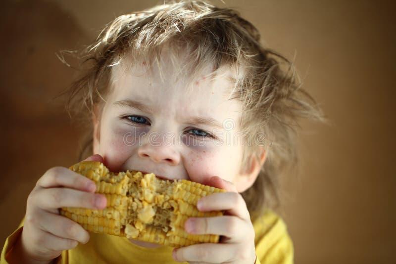 吃甜玉米的男孩金发碧眼的女人 免版税库存图片