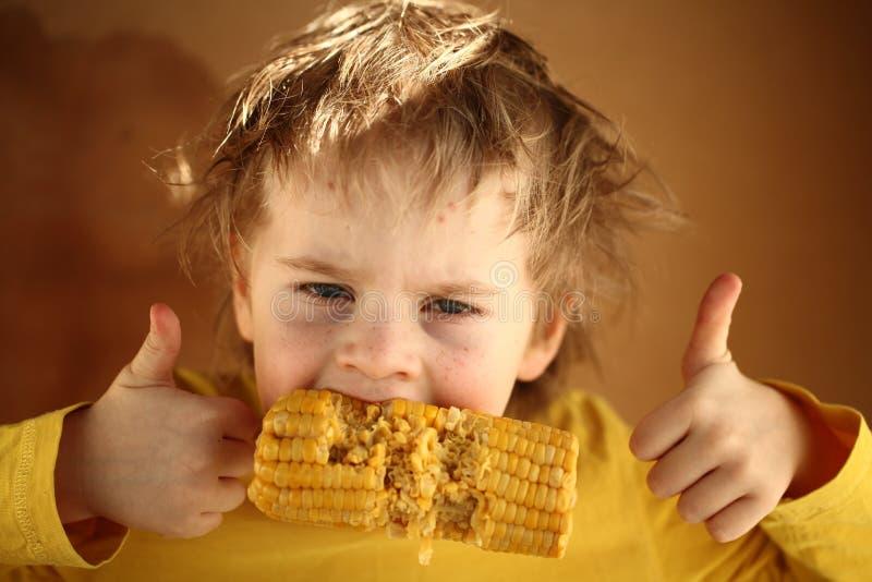 吃甜玉米的男孩金发碧眼的女人 库存照片