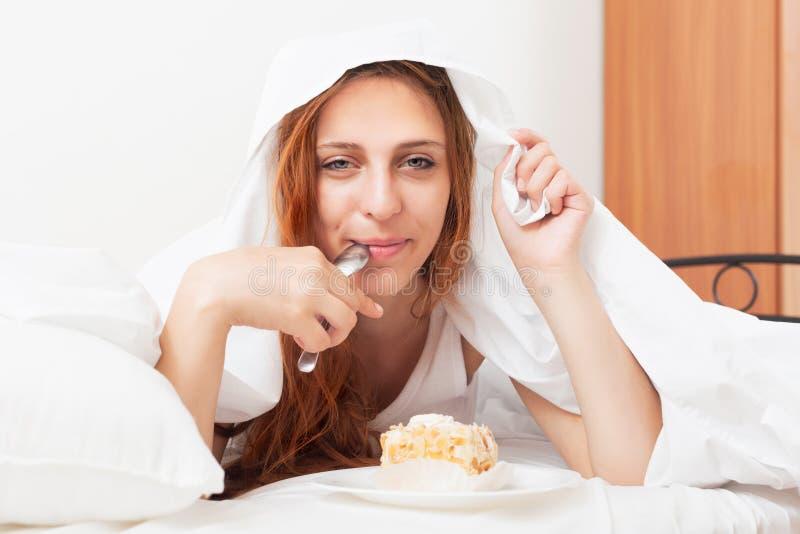 吃甜蛋糕的美丽的ong头发的妇女在板料下在床上 免版税图库摄影