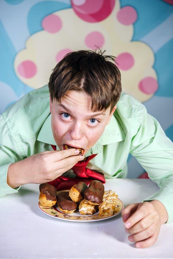 吃甜蛋糕,饥饿和糖店的滑稽的男孩 库存照片