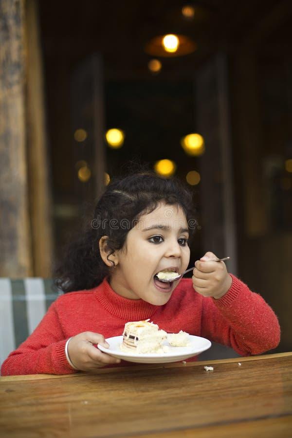 吃甜饼的女孩 免版税库存图片