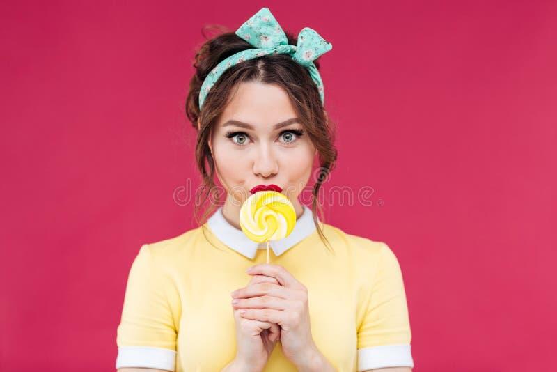 吃甜黄色棒棒糖的美丽的画报女孩画象  免版税库存照片