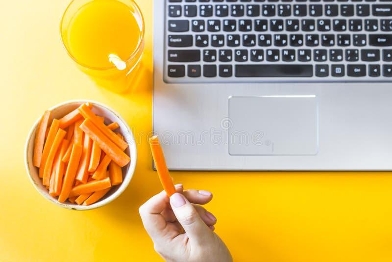 吃用在膝上型计算机的健康食物 库存照片