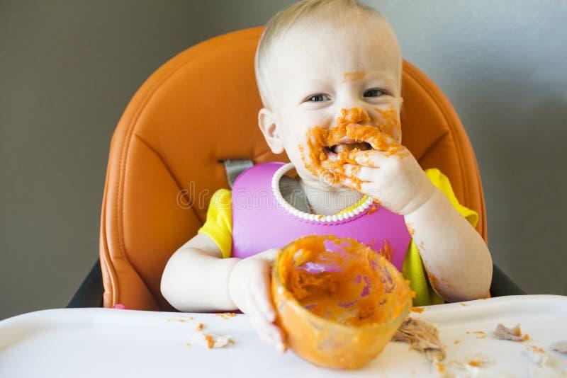 吃用在面孔的食物的婴孩 免版税图库摄影