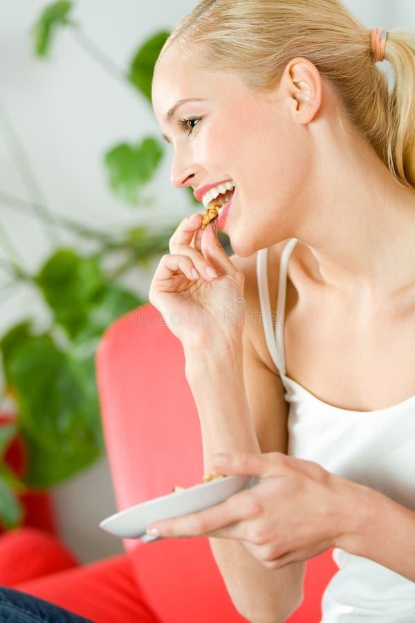 吃电视注意的妇女 免版税库存图片