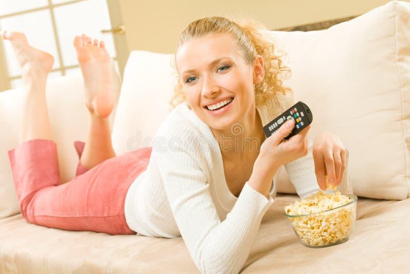 吃电视注意的妇女 库存图片