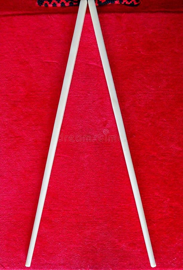 吃的汉语在红色背景黏附亚洲食物的筷子 库存图片