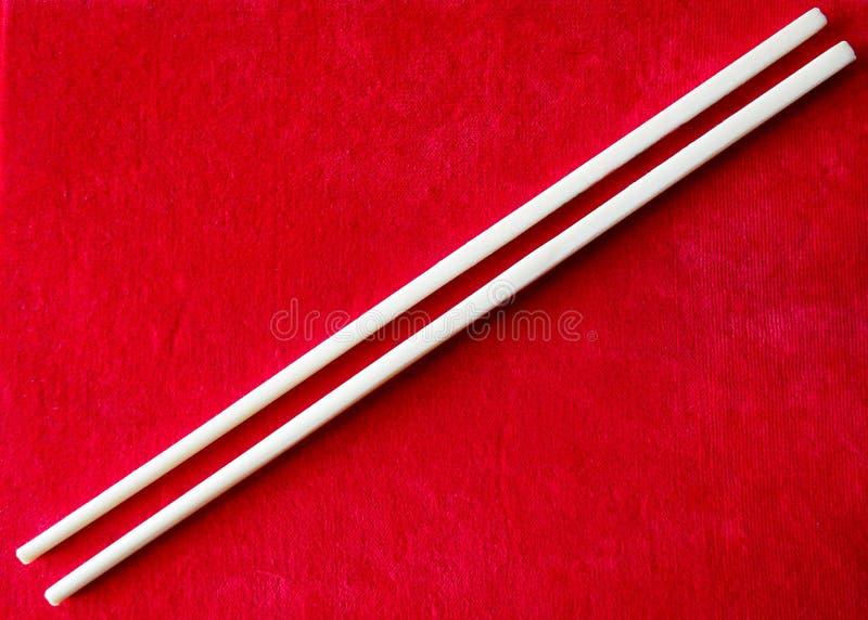 吃的汉语在红色背景黏附亚洲食物的筷子 免版税库存照片