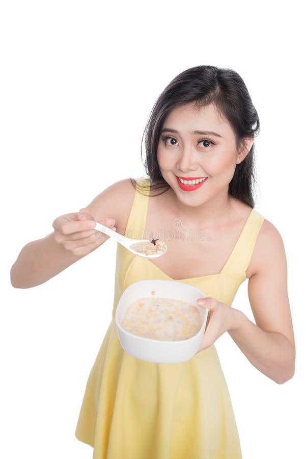 吃碗谷物或muesli的亚裔妇女早餐 免版税图库摄影
