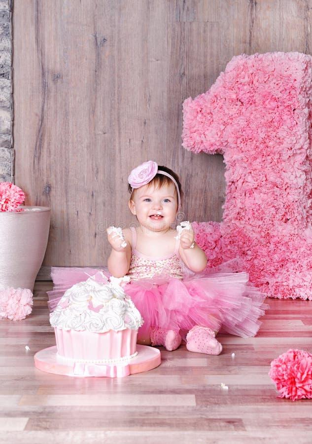 吃第一生日蛋糕的逗人喜爱的女婴 免版税库存照片