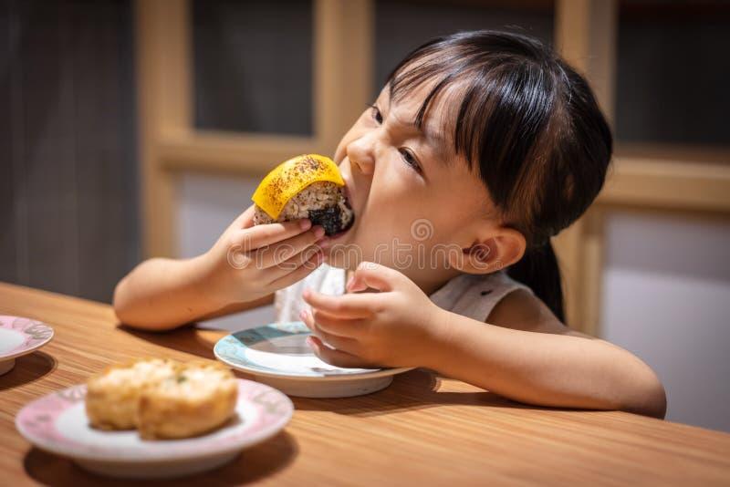 吃米饭团的亚裔矮小的中国女孩 免版税库存照片