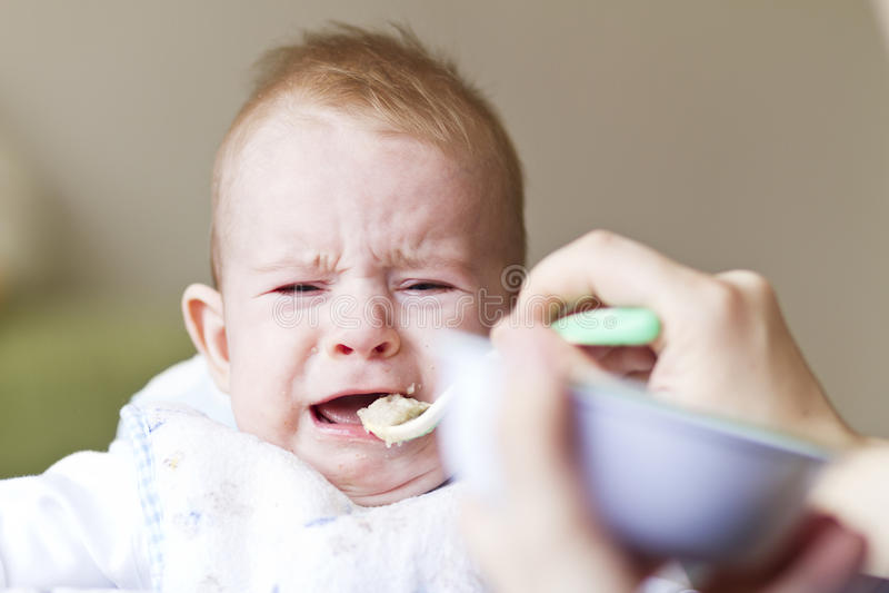吃粥的哭泣的婴孩 免版税库存照片