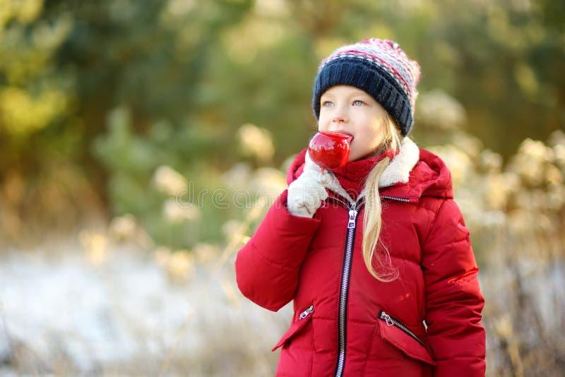 吃红色苹果的可爱的小女孩盖用糖结冰在美好的晴朗的圣诞节 库存照片