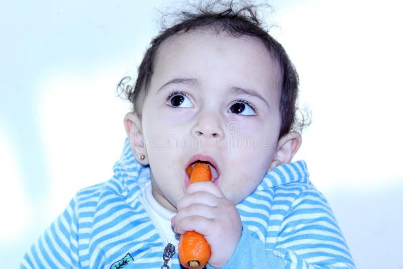 吃红萝卜的阿拉伯埃及女婴 免版税库存照片