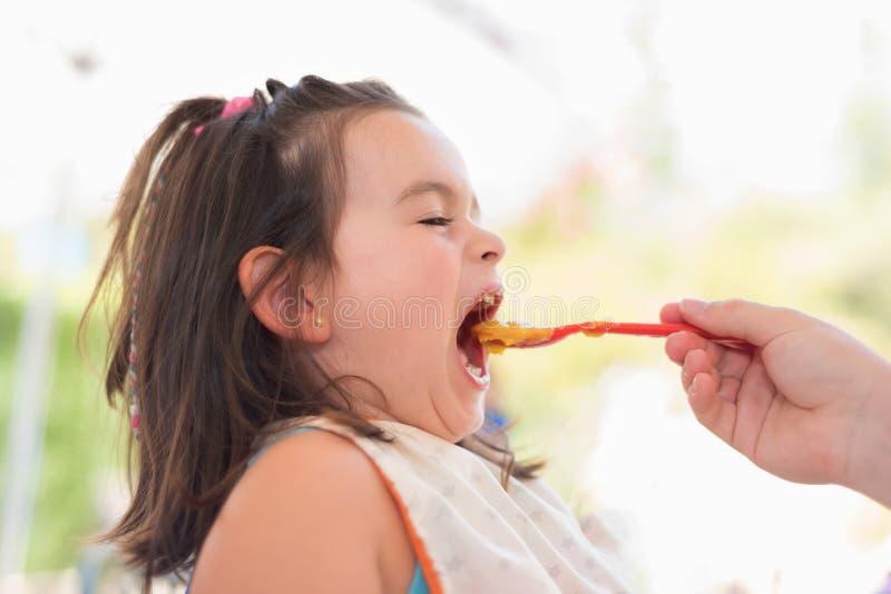 吃纯汁浓汤的逗人喜爱的小女孩 图库摄影