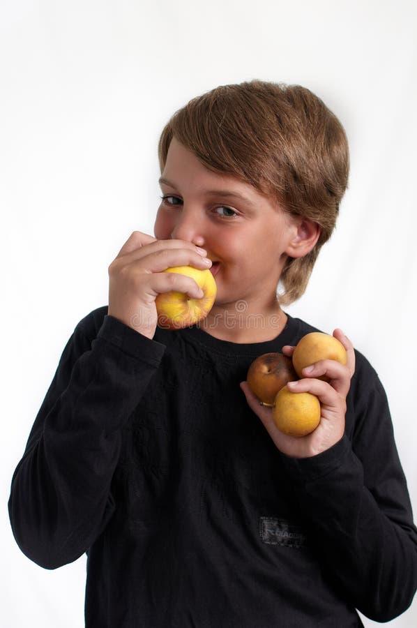 吃纵向的苹果男孩 免版税库存照片