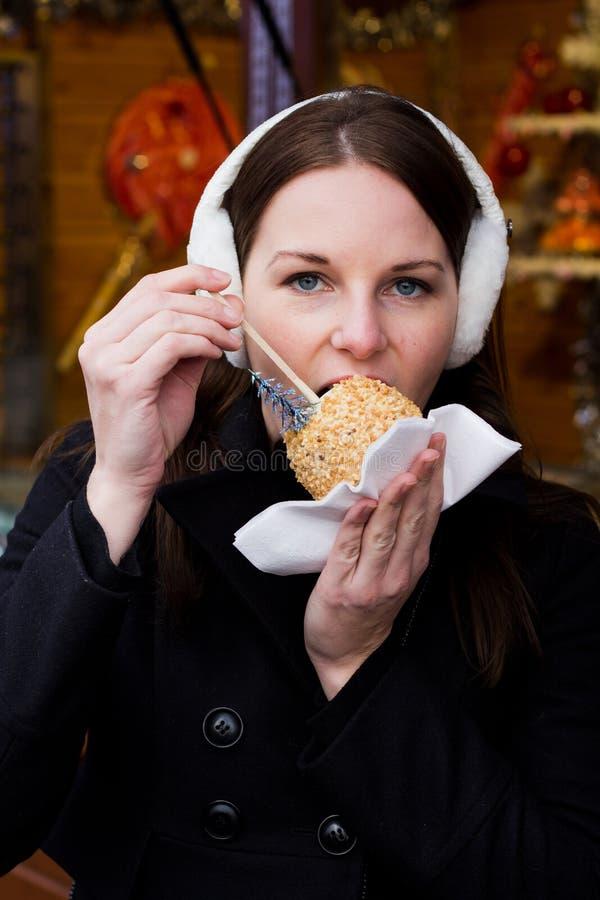 吃给上釉的妇女年轻人的苹果浅黑肤色的男人 免版税库存图片