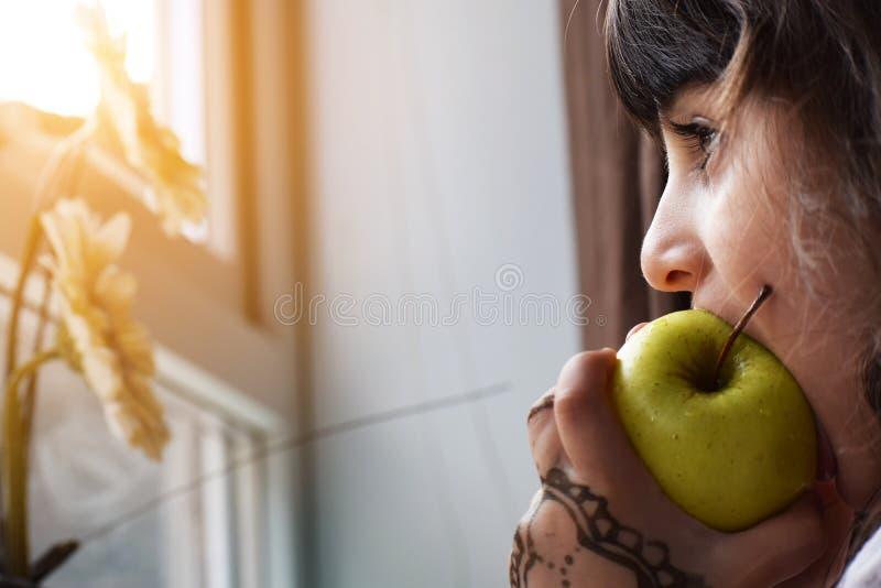 吃绿色健康苹果计算机的美丽的小女孩儿童孩子画象,当看外面从家庭窗口在晴天时 图库摄影