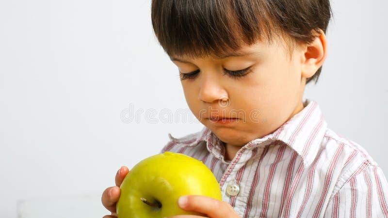 吃绿色苹果的俏丽的小男孩 免版税库存照片