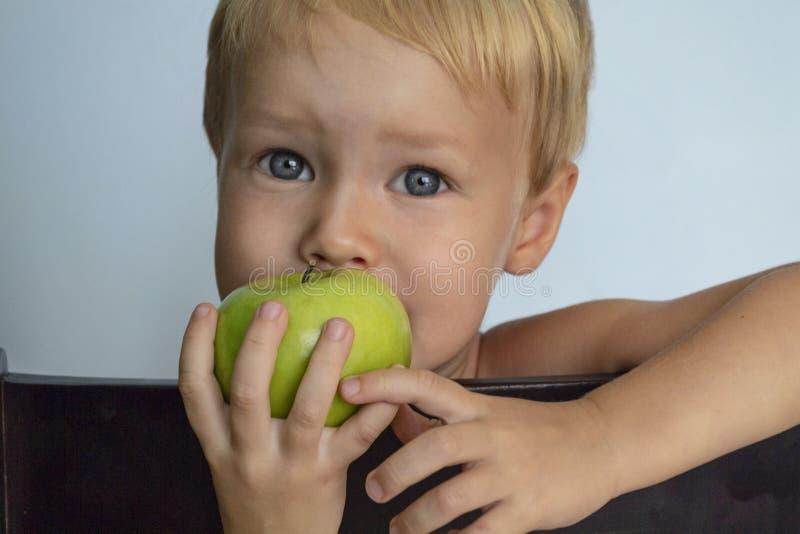 吃绿色苹果计算机的逗人喜爱的欧洲白肤金发的男孩 r 库存照片