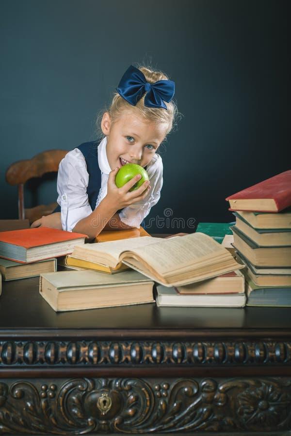 吃美味绿色苹果的逗人喜爱的学校女孩 免版税图库摄影