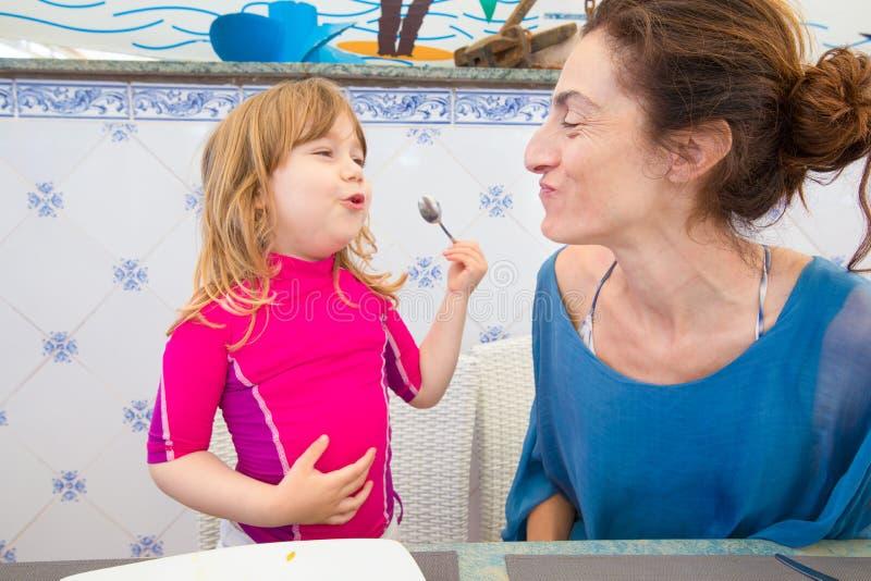 吃肉菜饭和微笑的小孩和母亲 免版税库存照片