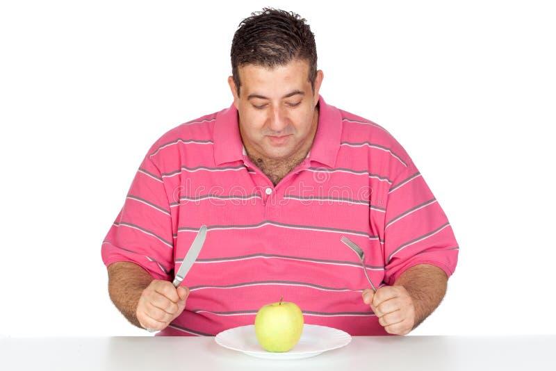 吃肥胖人的苹果 免版税库存照片