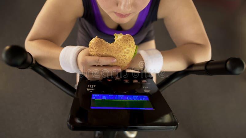 吃肥腻汉堡的肥头大耳的女性,当骑固定式自行车,快餐时 免版税库存照片