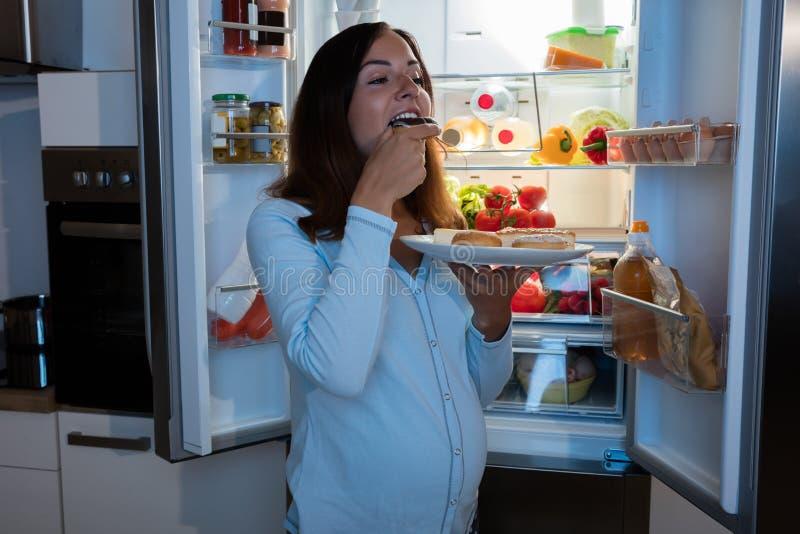 吃腌汁的孕妇在厨房里 免版税库存照片