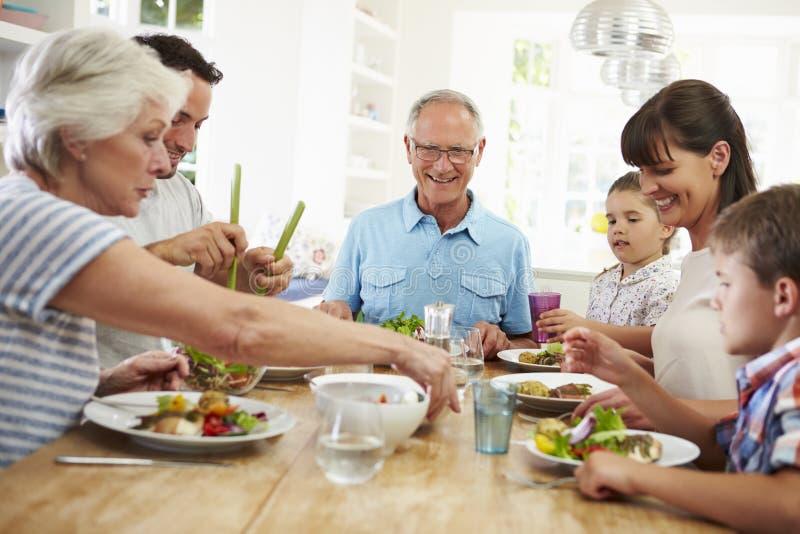 吃膳食的多一代家庭在厨房用桌附近 免版税库存照片