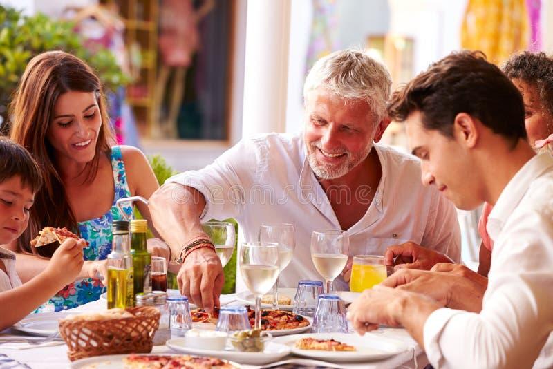 吃膳食的多一代家庭在室外餐馆 库存照片
