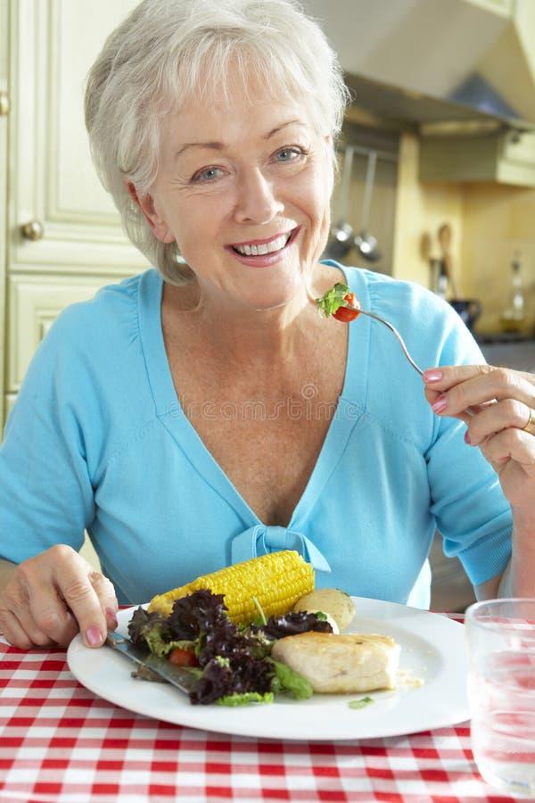 吃膳食的资深妇女在厨房里 免版税库存照片