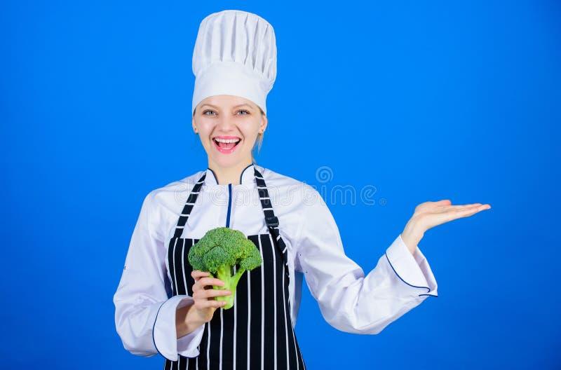 吃自然食物的Enjoy 在手中打手势用自然绿色硬花甘蓝的愉快的厨师 厨房佣人选择自然 库存图片