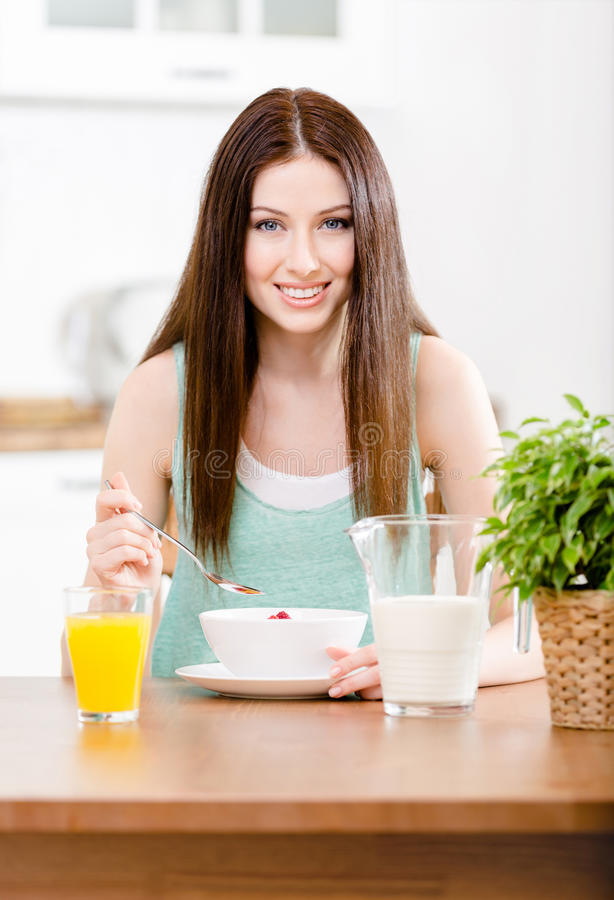 吃节食的谷物和橙汁的女孩 库存图片